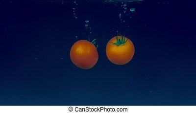 Tomatoes in slow motion floating in water