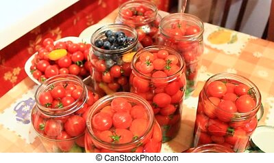 red tasty tomatoes in jars prepared for preservation