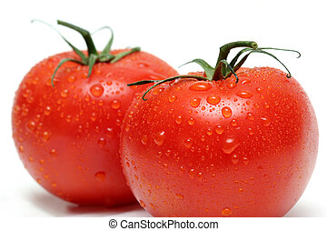 two tomatoes with water droplets, macro over white with shallow depth of field