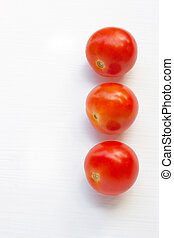 Tomatoes on white wooden background.