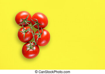 Tomatoes on yellow table top view