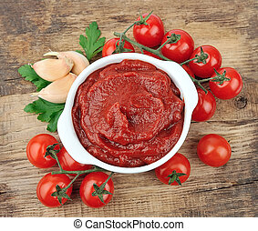 Tomatoes paste with spices and greens on wooden tables