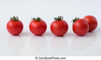 Tomatoes roll on white background in slow motion