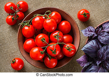 Tomatoes with basil in bowl on fabric background