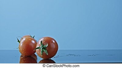 Tomatoes with droplets of water rolling on a glossy surface. Slow motion 2k video shooted on 240 fps