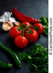 Tomatoes with vegetables on a dark background