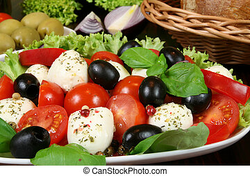 Caprese - Italian salad with cherry tomatos, olives and mozarella cheese