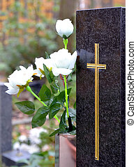 Tombstone with golden cross and white roses at cemetery