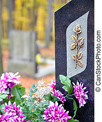 Tombstone with golden rose and purple flowers at cemetery