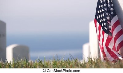 Tombstones and american flag, national memorial cemetery, military graveyard in USA. Headstones or gravestones, green grass. Respect and honor for armed forces soldiers. Veterans and Remembrance Day.