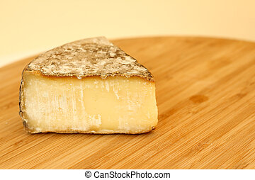 Tomme de savoie cheese on wooden board