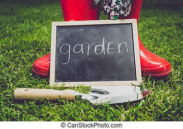 "blackboard with word ""Garden"" lying on grass next to garden tools"