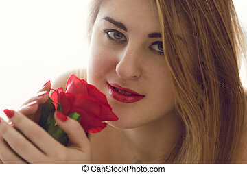 Toned closeup portrait of sexy woman holding red rose