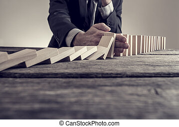 Toned image of a businessman stopping domino effect