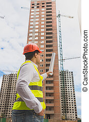 Toned image of architect pointing at building under construction