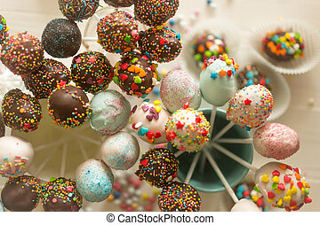 Toned image of decorated cake pops and candies on table