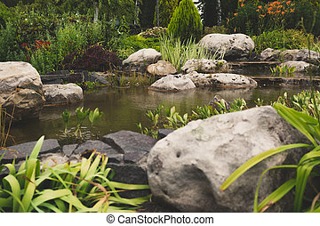 Toned image of formal garden with big rocks and fast stream