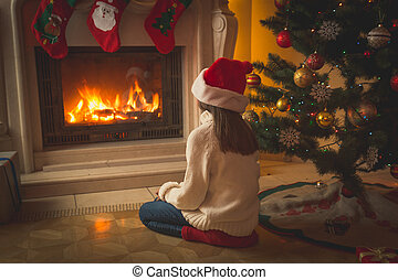 Toned image of girl in Santa hat sitting on floor and ...