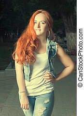 Toned image of red haired female posing in park