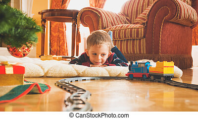 Toned image of smiling little boy playing on wooden floor with his new toy train and railroad. Child receiving presents and toys on New Year or Xmas