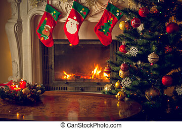 Toned image of wooden table in front of decorated fireplace and Christmas tree. Place for text. Suitable for Christmas background.
