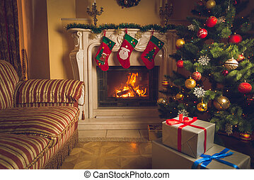 Toned interior photo of living room with burning fireplace, ...