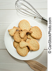 Toned photo from above of dish with cookies and kitchen utensils