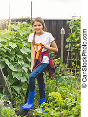Toned photo of beautiful teenage girl digging soil in garden with spade