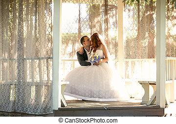 bride sitting on grooms legs on bench at gazebo