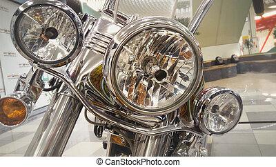 Closeup toned photo of chromed headlamp of chopper motorcycle