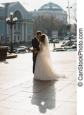embracing just married couple on street at cold sunny day