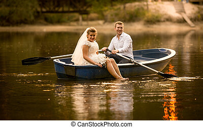 happy bride and groom sitting in wooden rowing boat at sunset