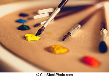 toned photo of paintbrushes lying on palette dipped in oil paint
