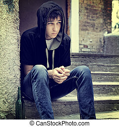 Toned Photo of Sad Teenager on the landing steps of the Old House