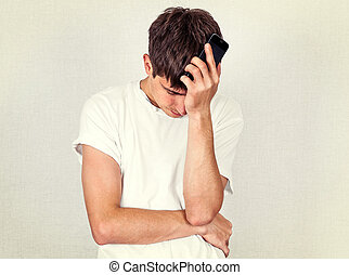 Sad Young Man - Toned Photo of Sad Young Man with a Phone by...
