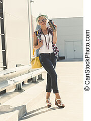 Toned photo of stylish hipster girl posing with coffee thermocup