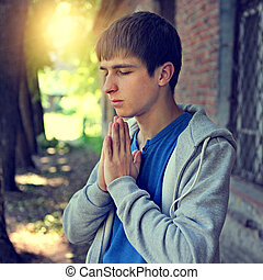 Young Man praying - Toned Photo of Young Man praying on the...