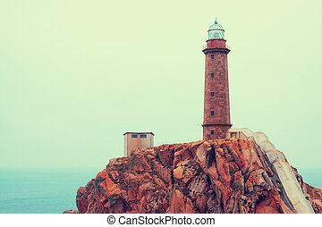 toned photo with lighthouse on rocky coast