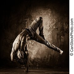 Toned picture of young man with naked torso doing acrobatic...