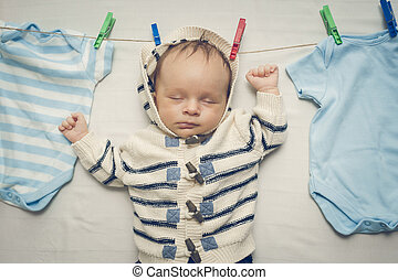 Toned portrait of baby boy hanging on clothesline