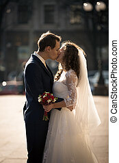 portrait of beautiful young bride and groom kissing on street