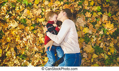 Toned portrait of beautiful young woman kissing her little son lying on leaves at autumn park