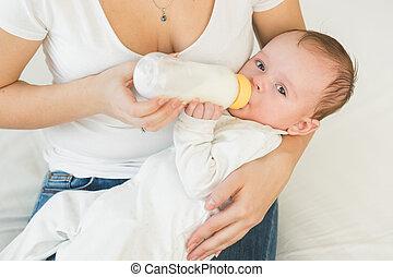 Toned portrait of cute baby boy drinking milk from bottle