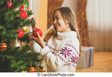 Toned portrait of cute girl in sweater decorating Christmas tree