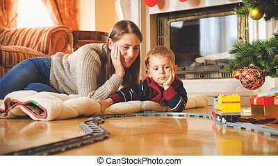 Toned portrait of family enjoying Christmas morning and playing with toy railroad. Child receiving presents and toys on New Year or Xmas