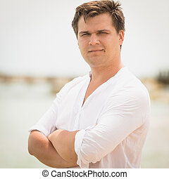toned portrait of handsome man in white shirt on the beach