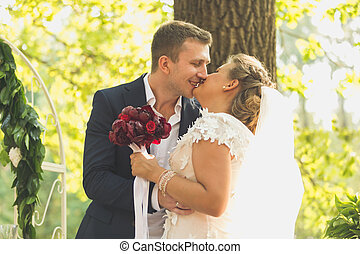 Toned portrait of happy bride and groom kissing at garden