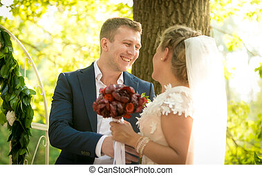 Toned portrait of happy bride and groom looking at each other at park