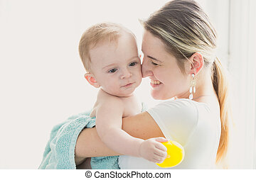 Toned portrait of happy smiling mother holding her baby after bathing