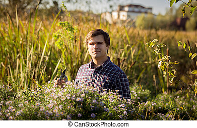 portrait of man working at garden and cutting flowers